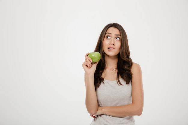 Porträt der verwirrten frau schauend grüner frischer apfel aufwärts halten und denken an das gesunde lebensmittel, das über weiß lokalisiert wird