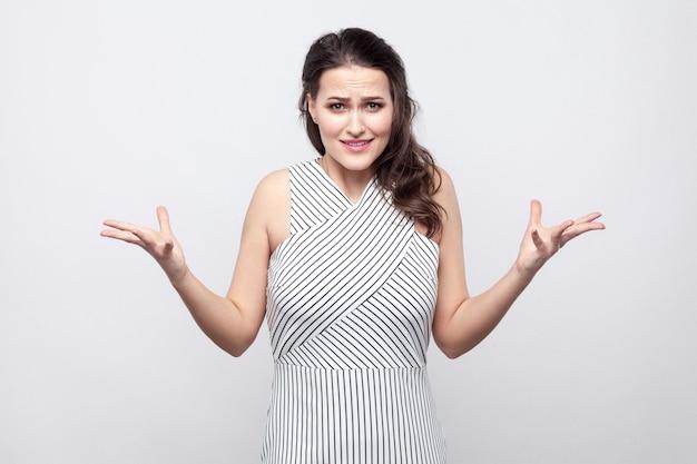 Porträt der verwirrten schönen jungen brunettefrau mit make-up und gestreiftem kleid, die mit verärgertem gesicht in die kamera steht und schaut. innenstudio erschossen, auf grauem hintergrund isoliert.
