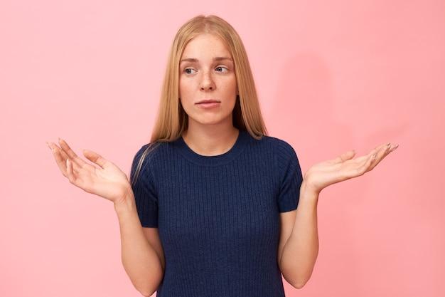 Porträt der verwirrten verwirrten niedlichen jungen frau, die für wörter ratlos ist, schultern zuckt und handbewegung macht, verwirrten gesichtsausdruck hat