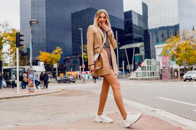 Porträt der vollen höhe der hübschen blonden frau, die über städtischer straße aufwirft. beige mantel und weiße turnschuhe tragen. trendige accessoires. sorglose dame, die die straße entlang geht.