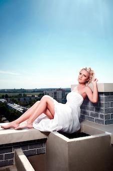 Porträt der vorbildlichen braut des blonden weiblichen mädchens der sexy schönen mode, die im weißen kleid im dach mit make-up und frisur aufwirft blauer himmel. sonne