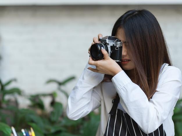 Porträt der weiblichen barista genießen ihr hobby mit dem fotografieren mit der digitalkamera im café