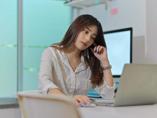 Porträt der weiblichen büroangestellten arbeiten von zu hause mit laptop und computer im heimbüroraum