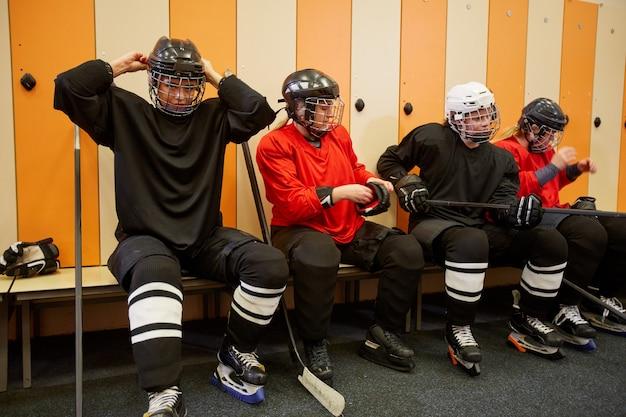 Porträt der weiblichen eishockeymannschaft in voller länge, die sich auf das spiel in der umkleidekabine vorbereitet