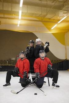 Porträt der weiblichen eishockeymannschaft in voller länge, die während des trainings auf der eisbahn aufwirft