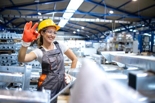 Porträt der weiblichen fabrikarbeiterin, die okay zeichen zeigt