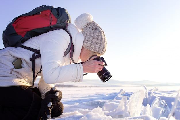 Porträt der weiblichen fotografschießen-winterlandschaft nahe bei dem gefrorenen baikalsee. wintertourismus in russland