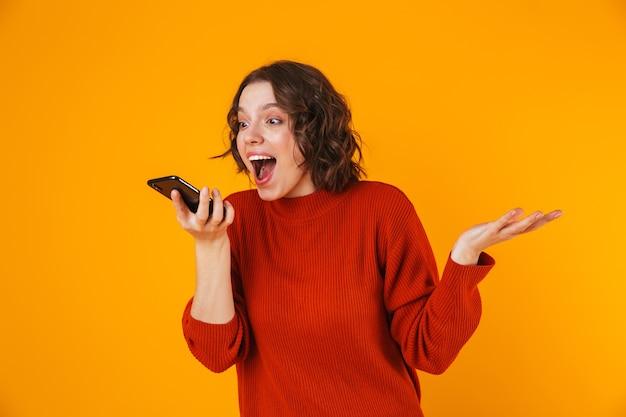 Porträt der weiblichen frau 20s, die pullover hält, der auf handy hält und spricht, während isoliert über gelb steht