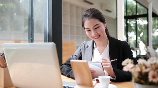 Porträt der weiblichen führungskraft, die über arbeitszeitplan für mitarbeiter denkt, der bericht in notizbuch schreibt, während laptop verwendet wird.