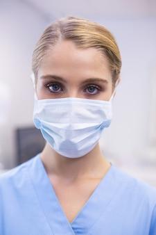 Porträt der weiblichen krankenschwester, die chirurgische maske trägt