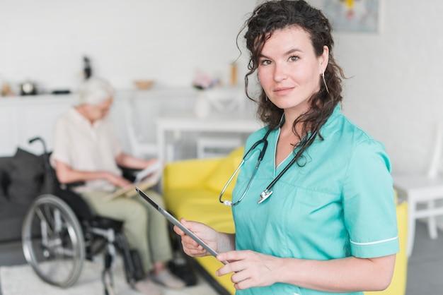 Porträt der weiblichen krankenschwester die digitale tablette halten, die vor älterem patienten auf rollstuhl steht