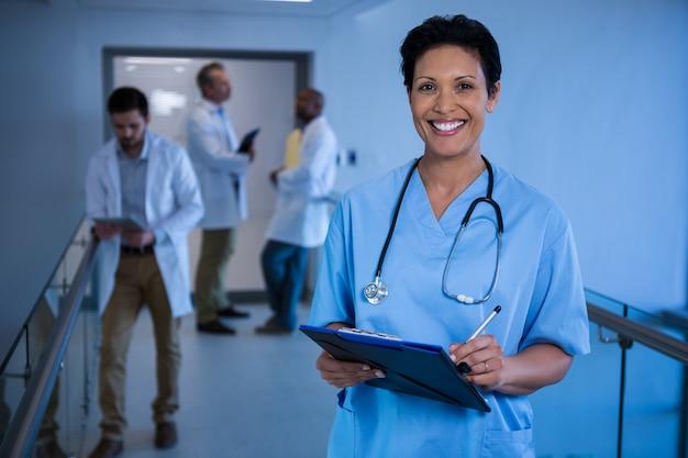 Porträt der weiblichen krankenschwester, die in zwischenablage im korridor schreibt