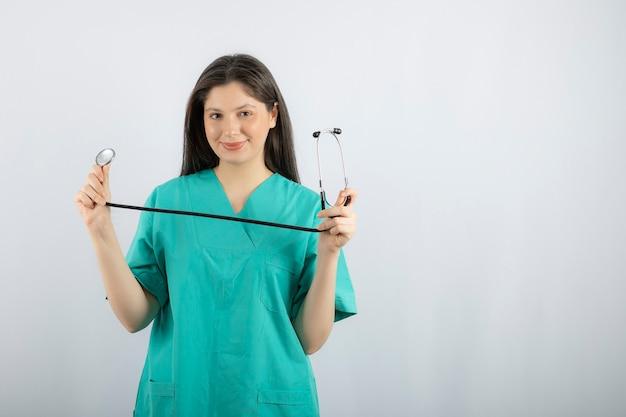 Porträt der weiblichen krankenschwester mit dem stethoskop, das auf weiß aufwirft.