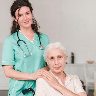 Porträt der weiblichen krankenschwester mit ihrem älteren patienten, der auf rollstuhl sitzt