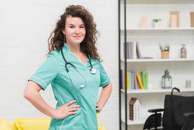 Porträt der weiblichen krankenschwester mit ihrer hand auf hüften in der klinik
