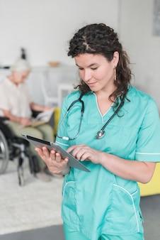 Porträt der weiblichen krankenschwester mit stethoskop um ihren hals unter verwendung der digitalen tablette