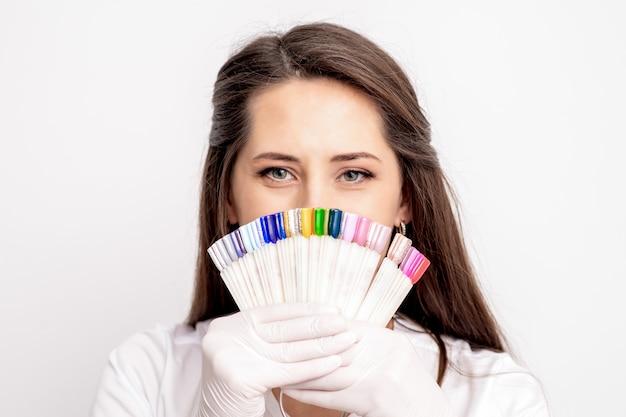 Porträt der weiblichen maniküre-meisterin, die ihr gesicht mit nagelprobenpalette bedeckt