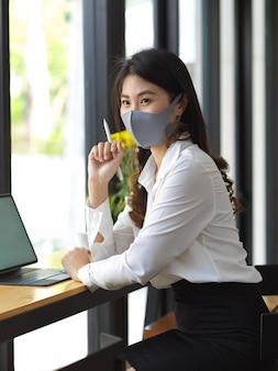Porträt der weiblichen tragenden maske, die mit digitaler tablette im café arbeitet