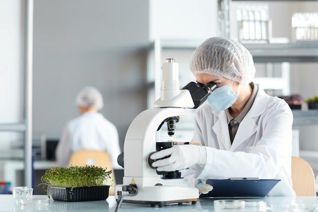 Porträt der wissenschaftlerin, die im mikroskop schaut, während pflanzenproben im biotechnologielabor, kopierraum studieren