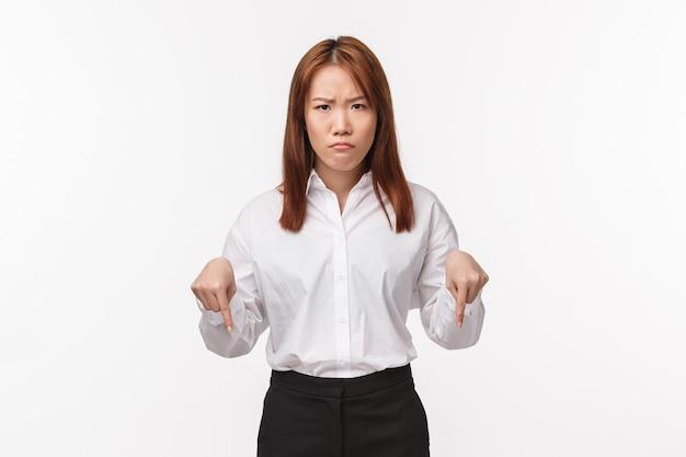 Porträt der wütenden mürrischen asiatischen unternehmerin, die angestellten schimpft, nach unten zeigt und die stirn runzelt, die schmollmund schmollt, hier geste als von schlechtem projekt enttäuscht ansehen,