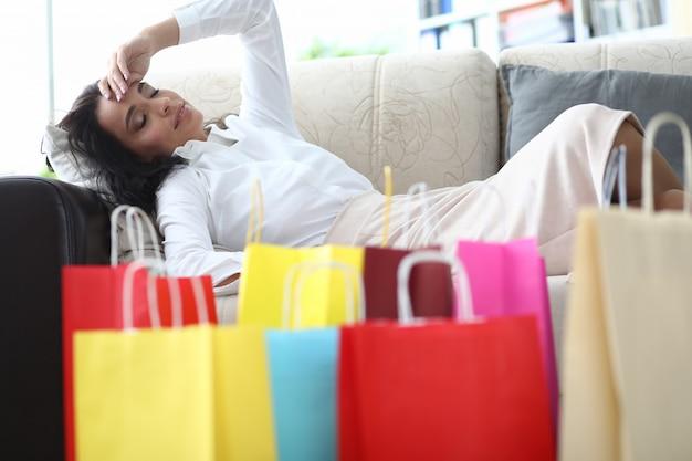 Porträt der wunderbaren müden frau, die nachdem dem einkaufen sich entspannt. schöne dame, die zeit für das ausruhen auf bequemem aufenthaltsraum hat. einkaufs- und modekonzept