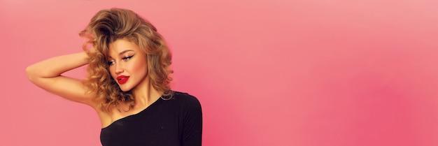 Porträt der wunderbaren schönen frau mit den großen roten lippen. modernes helles make-up auf ihrem hübschen gesicht, lockige frisur. schlanker sexy körper mit schwarzem oberteil und offener schulter.