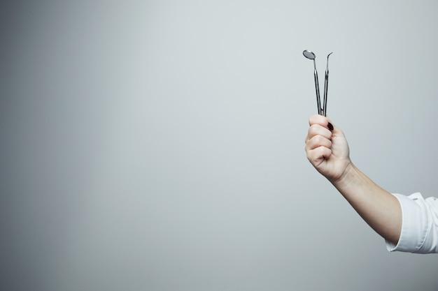Porträt der zahnärztin. sie steht in ihrer zahnarztpraxis. weiblicher zahnarzt, der ein weißes gewand trägt