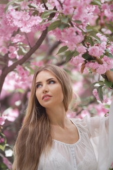 Porträt der zarten frau gegen die sakura-blume