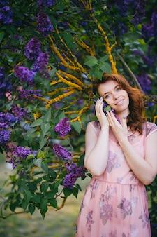 Porträt der zarten schönen frau im rosa kleid, das in fliederbüschen aufwirft.