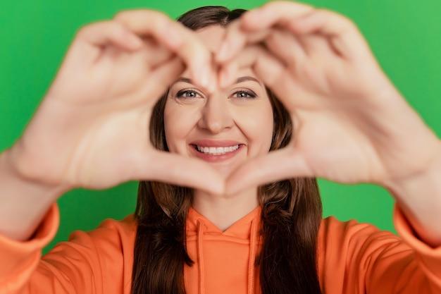 Porträt der zarten süßen teenagerdame zeigt herzgeste-abdeckungsgesicht auf grünem hintergrund