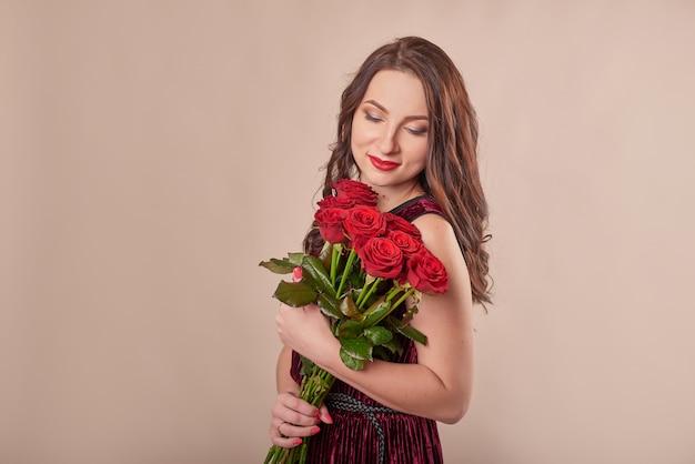 Porträt der zufriedenen jungen frau im roten kleid mit rosenstrauß