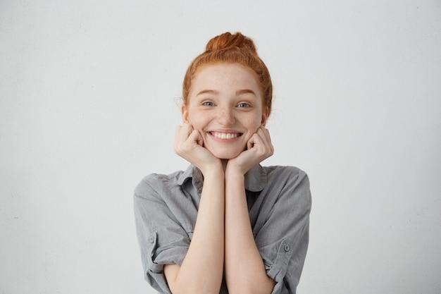 Porträt der zufriedenen rothaarigen frau mit ingwerhaar, das mit ihren blauen warmen augen und aufgeregtem lächeln schaut, das aufrichtigen und sanften blick hände unter kinn hält. menschen, schönheit, emotionen konzept