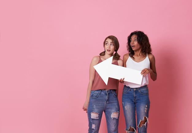 Porträt der zwei entsetzten jungen frau, die mit ihrem pfeil zeigt auf den kopienraum lokalisiert über rosa steht.