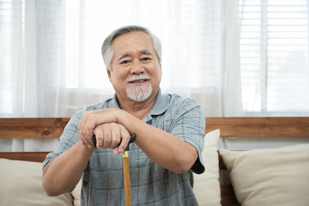 Porträt des älteren älteren asiatischen mannes sitzen auf kutscherhand halten gehstockblick kamera mit lächeln.