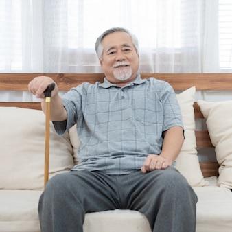 Porträt des älteren alten älteren asiatischen mannes sitzen auf trainerhand halten helfen gehstock sitzen auf sofa im haus mit glück und gesundem lebensstil.
