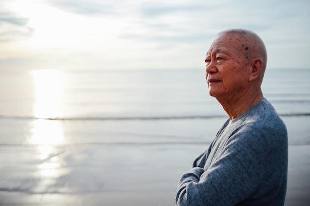 Porträt des älteren alten mannes entspannen sich auf dem strandlächeln und dem glücklichen gesicht