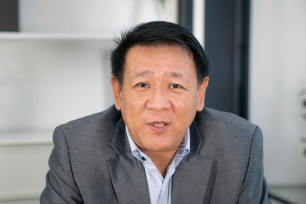 Porträt des älteren asiatischen geschäftsmannes, der im besprechungsraum mit online-besprechung durch videokamera spricht