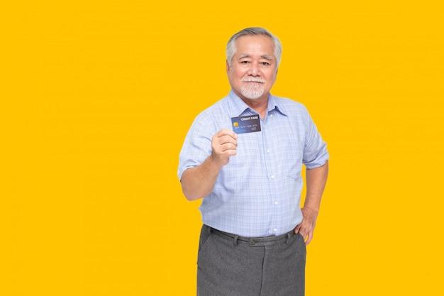 Porträt des älteren asiatischen mannes, der kreditkarte hält und auf hand lokalisiert auf gelber wand zeigt