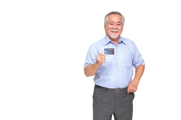 Porträt des älteren asiatischen mannes, der kreditkarte hält und auf hand lokalisiert auf weißer wand zeigt