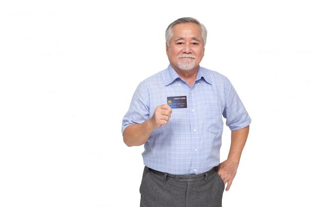 Porträt des älteren asiatischen mannes, der kreditkarte hält und zur hand zeigt