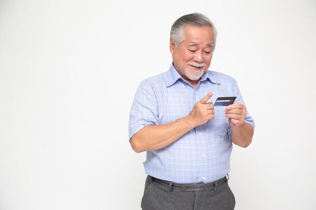 Porträt des älteren asiatischen mannes, der kreditkarte hält