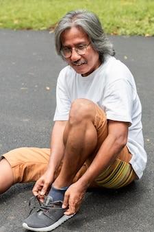 Porträt des älteren asiatischen sportmannes, der spitzee auf der straße bindet.