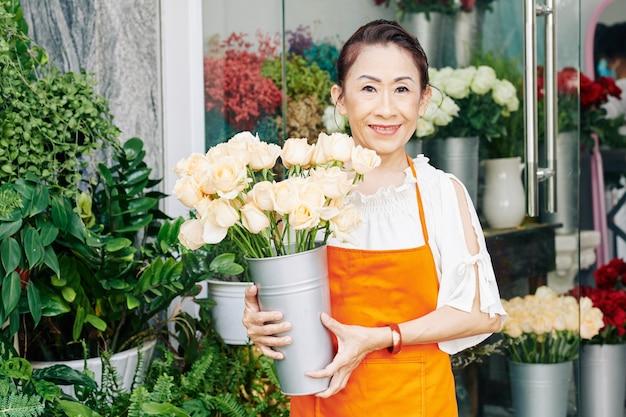 Porträt des älteren floristen, der am eingang ihres blumenladens mit eimer mit frischen weißen rosen steht
