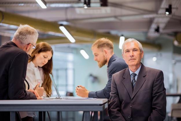 Porträt des älteren geschäftsmannes mit seinem team im büro