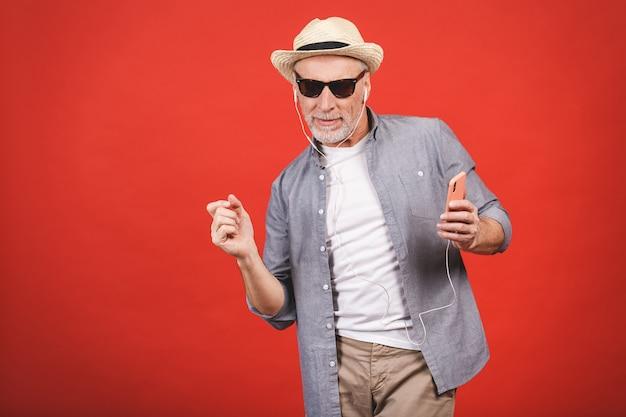 Porträt des älteren glücklichen fröhlichen älteren mannes tanzend und hörende musik mit telefon und kopfhörern isoliert.