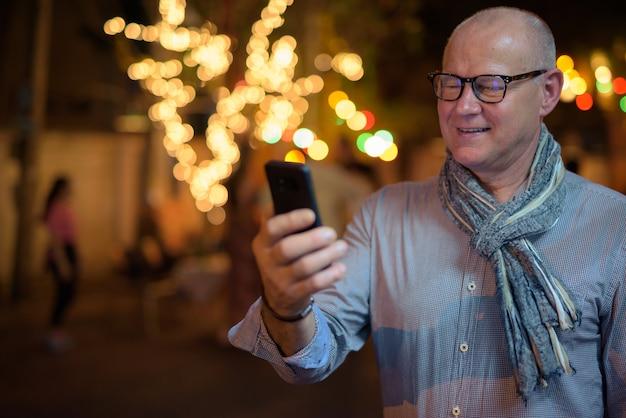Porträt des älteren gutaussehenden skandinavischen touristenmannes, der die stadtstraßen in der nacht erkundet