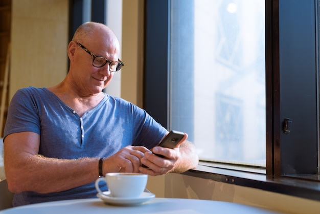 Porträt des älteren gutaussehenden skandinavischen touristenmannes, der sich innerhalb des coffeeshops entspannt