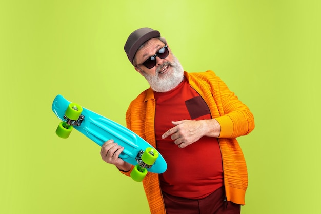 Porträt des älteren hipster-mannes, der einen skate lokalisiert auf grünem hintergrund hält.