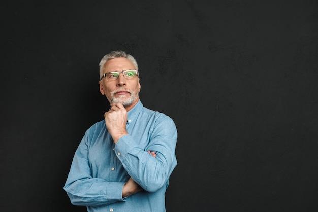 Porträt des älteren mannes 70er jahre mit grauem haar und bart, der sein kinn berührt und mit nachdenklichem blick nach oben schaut, isoliert über schwarzer wand