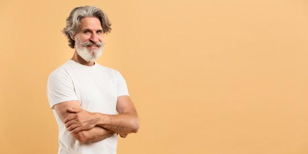 Porträt des älteren mannes, der arme kreuzt und mit kopienraum lächelt